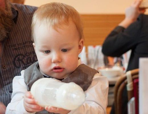 Kind untersucht Babyflasche | familiert.de