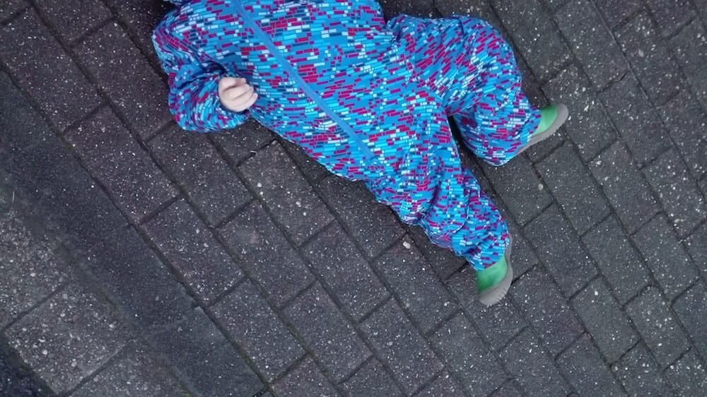 Kind liegt auf der Straße
