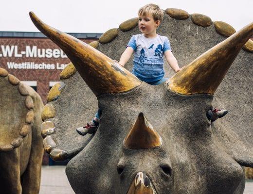 Kind sitzt auf einem Dinosaurier | familiert.de